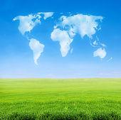 Gebied van gras met wereld gevormd wolken — Stockfoto