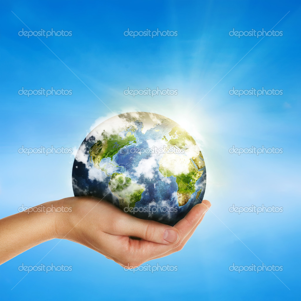 Hand holding globe over blue sky