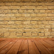 Vintage brown grungy textured brick interior with wooden floor — Stock Photo