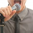 Businessman or singer screaming holding microphone with his hand — Stock Photo #8066655