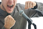 Businessman screaming in microphone with his fist rased up isola — Photo