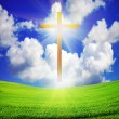 Easter cross over green field and blue sky — Stock Photo