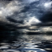 Dark cloudy stormy sky with clouds and waves in the sea — Stock Photo