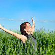 Stock Photo: Woman with hands raised up in the wheat field