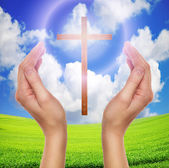 Hands praying with cross in sky - easter concept — Stock Photo