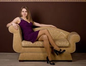 An attractive young woman sitting on sofa in a lovely dress. — Stock Photo