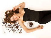 Beautiful woman lie on coffee beans with coffee cup — Stock Photo