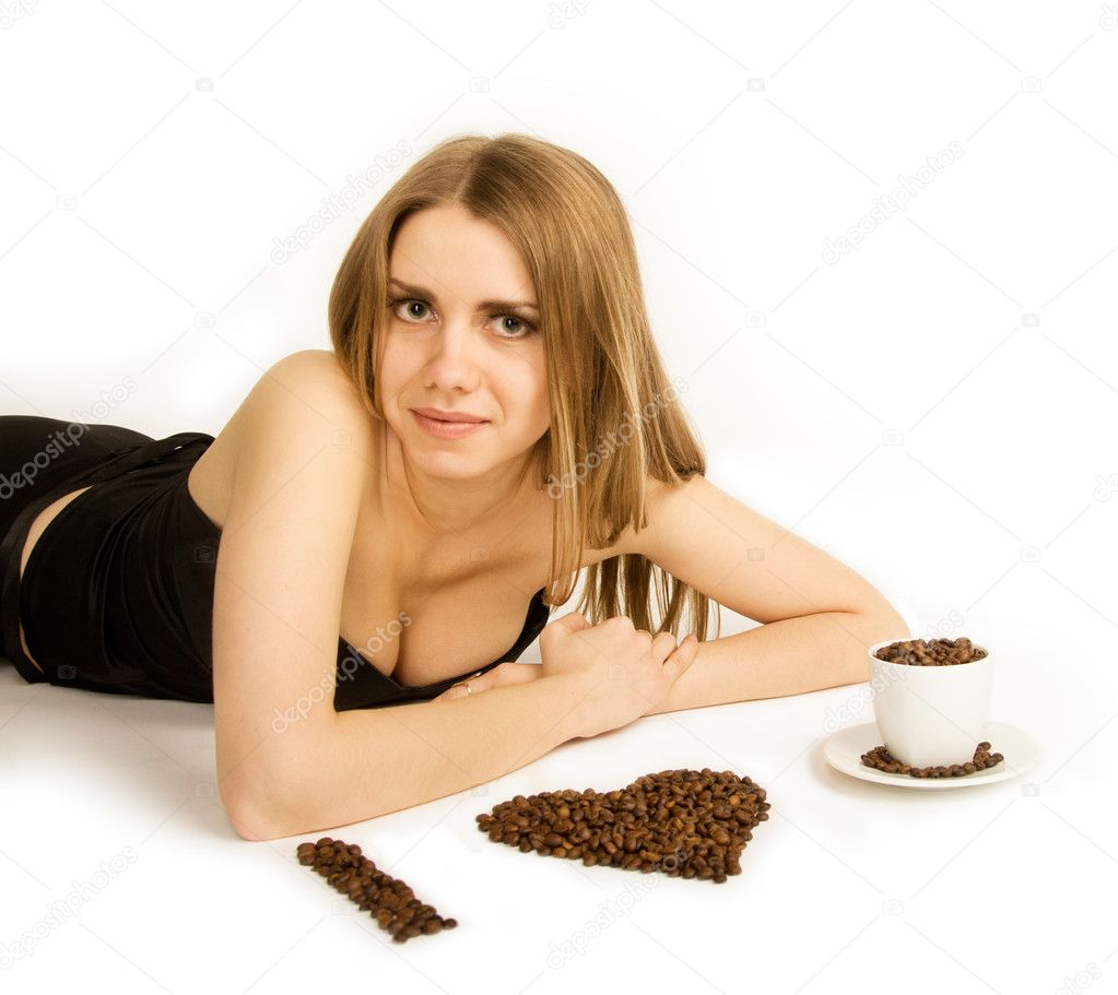 Beautiful woman lie on white background wiht coffee beans and cup. She is looking at camera. — Stock Photo #10228371