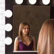 An attractive young woman looking in the mirror — Stock Photo