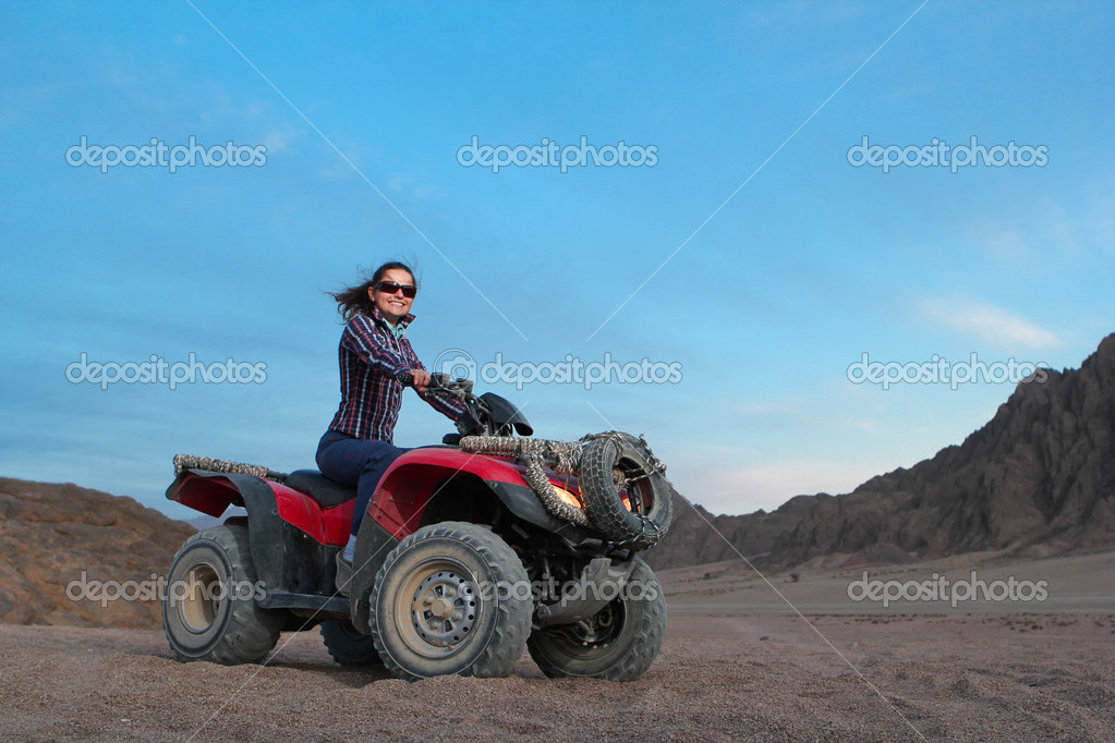 Pretty positive girl on atv on the desert sunrise background  Stock Photo #9174672