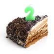 Slice of chocolate birthday cake with number two candle — Stock Photo
