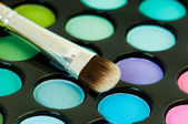Multicolored eye shadows with cosmetics brush — Stock Photo