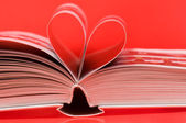 Pages of a book curved into a heart shape on red — Stock Photo