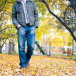 Young man walking in the autumn park — Stock Photo