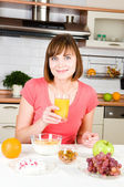 Young woman drinking orange juice with cereal muslin at home — Stock Photo