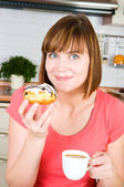 Young woman enjoying a cup of coffee and doughnut — Stock Photo