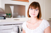 Young attractive brunette in the kitchen — Stock Photo