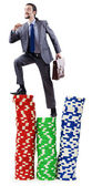 Stacks of casino chips and climbing businessman — Stockfoto