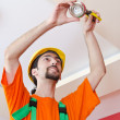 Electrician working on cabling lighting - Stock Photo