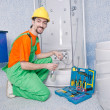 Plumber working in the bathroom - Stock Photo
