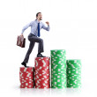 Stacks of casino chips and climbing businessman - Stockfoto