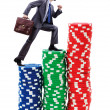 Businessman climbing stacks of casino chips — Stock Photo #10573435