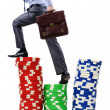 Stacks of casino chips and climbing businessman — Stock Photo #10573443
