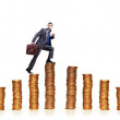 Businessman climbing gold coins stacks - Stockfoto