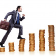 Businessman climbing gold coins stacks — Stock Photo