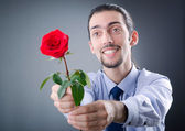 Young man with red rose — Stock Photo