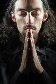 Jeune homme priant dans l'obscurité — Photo