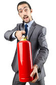 Man with fire extinguisher in firefighting concept — Stock Photo