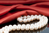 Pearls necklace on satin background — ストック写真