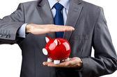 Man saving his money in the piggybank — Stock Photo