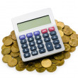 Coins and calculator on white - Stock Photo