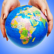 Stockfoto: Hand holding globe against gradient