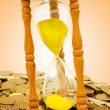 Stock Photo: Time is money concept - hourglass and coins