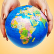 Hand holding globe against gradient — Stockfoto #9094567