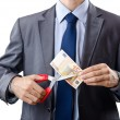 Man cutting money on white — Stock Photo