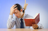 Businessman reading bible before hanging himself — Stock Photo