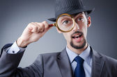 Detective and magnifying glass — Stock Photo