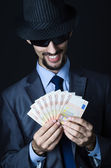 Man with counterfeir money — Stock Photo