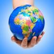 hand innehav världen mot lutning — Stockfoto