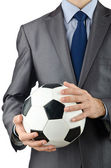 Businessman holding football on white — ストック写真