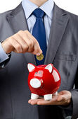 Man saving his money in the piggybank — Stock Photo