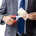 Man cutting money on white — Stock Photo #9181618