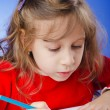 Photo: Little girl drawing with pencils