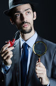 Detective with magnifying glass and pipe — Stock Photo
