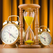 Stock Photo: Alarm clocks and hourglass in time concept