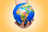Hand holding globe against gradient — Stock Photo